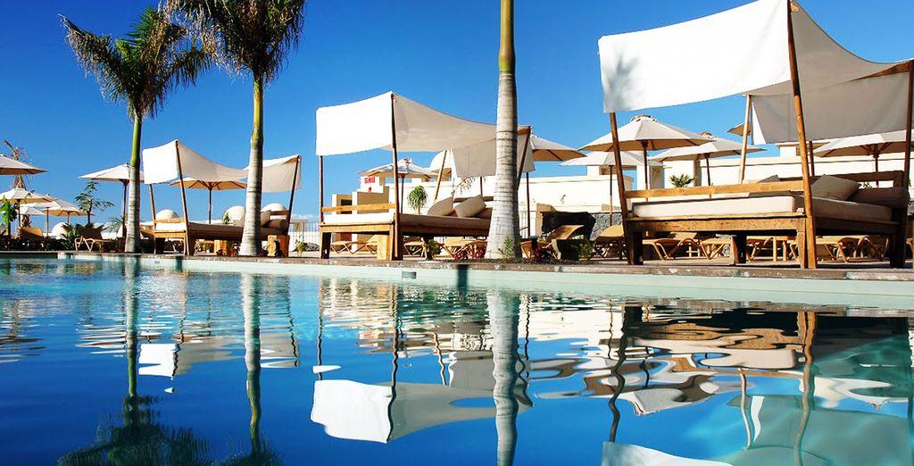 Relájese en las camas balinesas al borde de la piscina