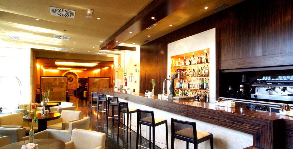 Toma una copa en el bar del hotel