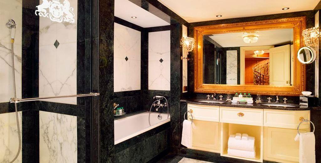 Un amplio baño de mármol con albornoces y zapatillas