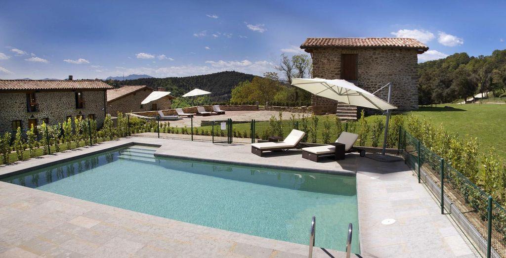 Prenez du bon temps sur les bains de soleil installés au bord de l'eau, entouré par les montagnes