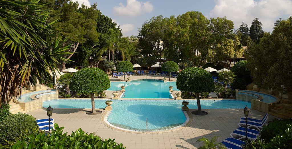 Het zwembad is omringd door groene tuinen